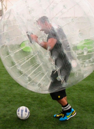 Man from a stag party playing Bubble Football with the ball at his feet