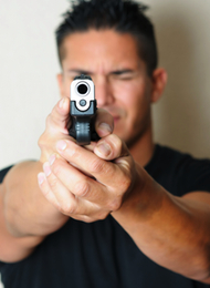 Man Shooting A Pistol at the camera