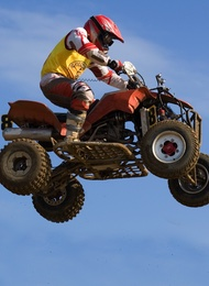 Quad Bike & Rider In Mid Air With A Sky As Background