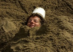 Man buried in the sand as a stag do prank