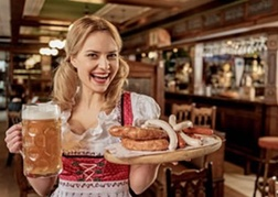 German lady holding a stein of beer and a platter of sausages