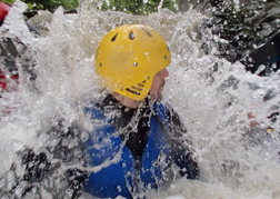 Man sliding down a water chute whilst Canyoning on a stag party