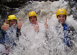 3 Men standing under a small waterfall as part of a stag weekend