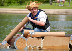 stag dressed up on a stag weekend doing a Cardboard Boat Challenge
