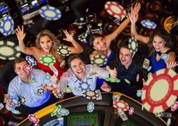 Group throwing Casino chips in the air in celebration