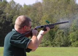 Man shooting a shotgun at a clay