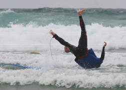man being flipped off a surfboard