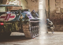 man playing Urban Paintball crouching behind a tank on his stag do