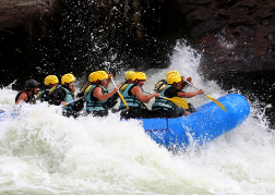 group White water rafting hitting frothing water whilst on a stag weekend