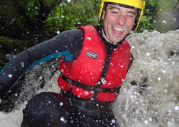 Man sliding down a water chute whilst Canyoning on a stag weekend