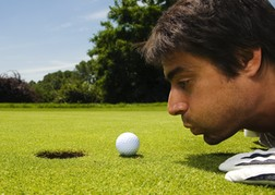 Golfer Blowing Ball In To Hole