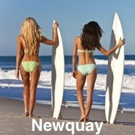 2 Ladies with their back to us holding up surf boards