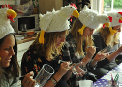 A Hen Party with humorous hats painting glasses in a craft hen activity