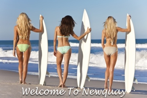 3 Ladies in bikinis holding up surfboards on Newquay Beach