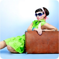 lady in a bright green dress leaning on her suitcase