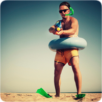 man on beach in rubber ring and holding up a water shooter