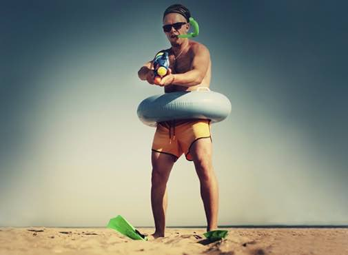 Groom on beach in fancy dress with water shooter, funny picture