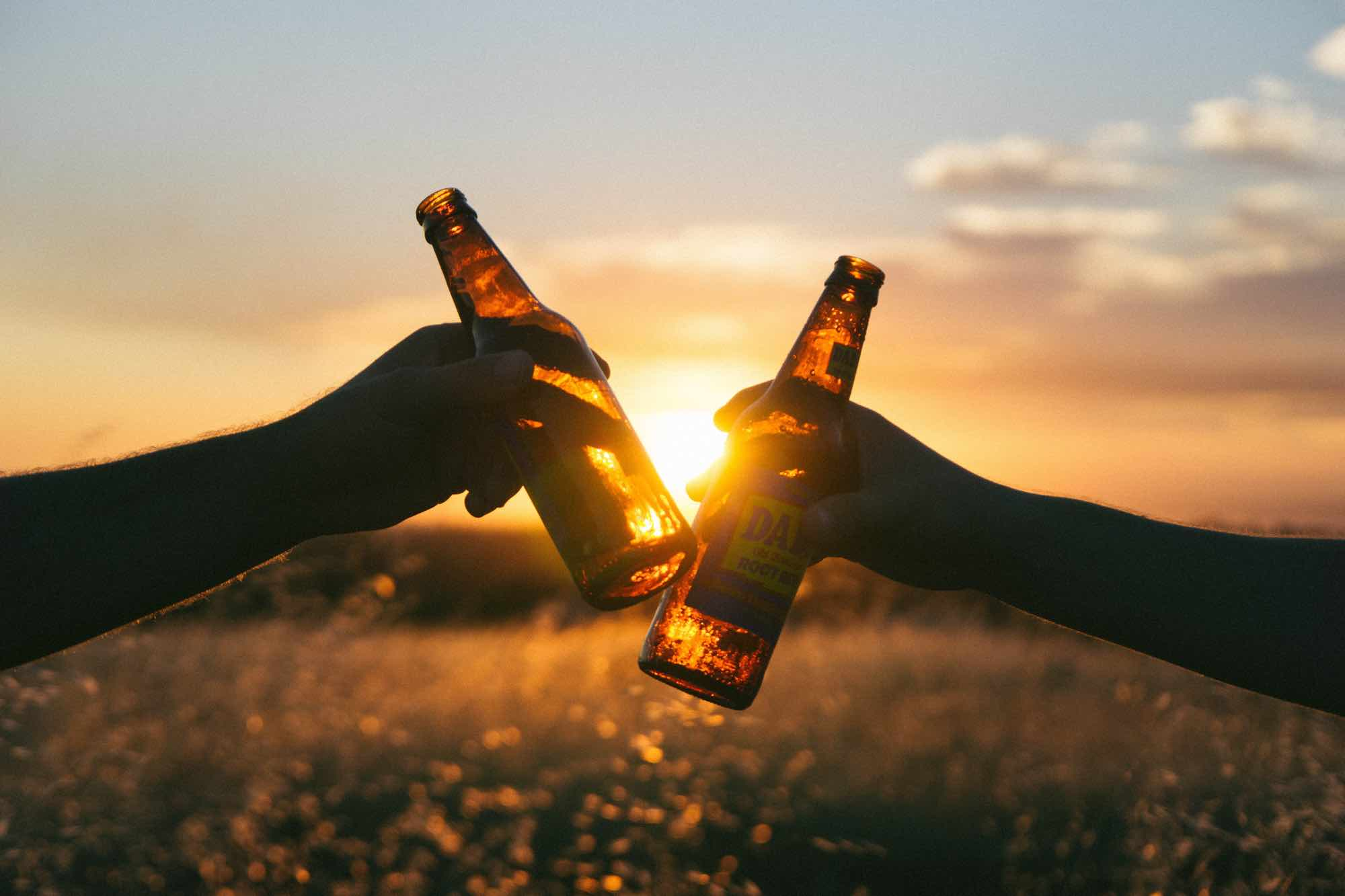 2 bottle of beer being clinked at a sunset